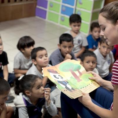 Barnomsorgsvolontär som åkt på en kort volontärresa läser en saga för barnen i hennes klass.